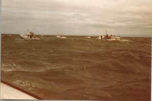 visserskotters, de begeleidende boten, hebben moeite met de hoge golven